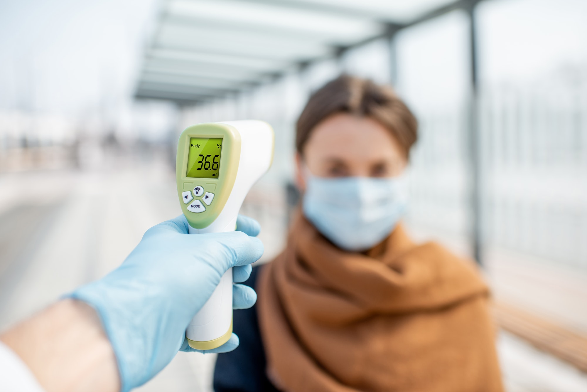 Measuring temperature of a young woman in face mask at a checkpoint outdoors